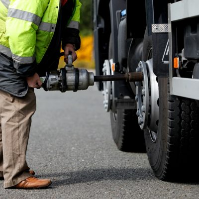 Mechanic in high-vis changing a tire on a truck